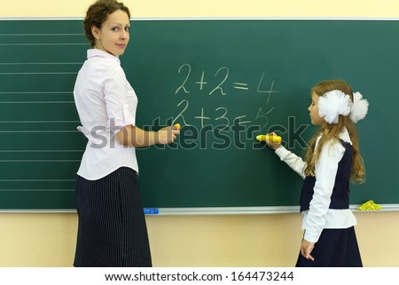 Girl and teacher stand near chalkboard and solve simple math examples in classroom at school. - stock photo