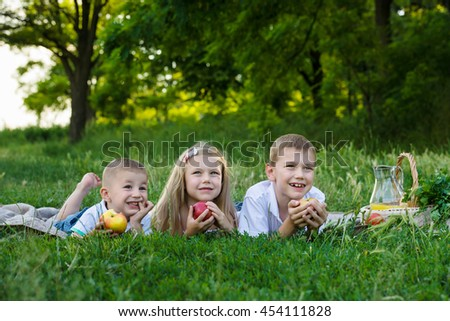 girl and two boys lay on stomach on the green grass and eat apples