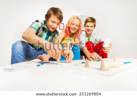 Girl and two boys playing table game at home - stock photo