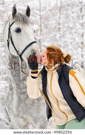 Girl and white horse in winter - stock photo