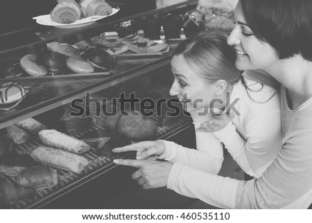 Girl and woman gladly selecting pastry in the bakery