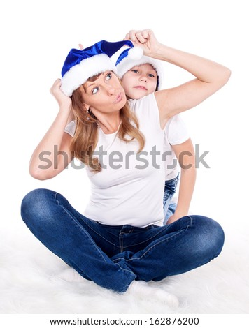 Girl and woman in Santa caps. Isolated white background