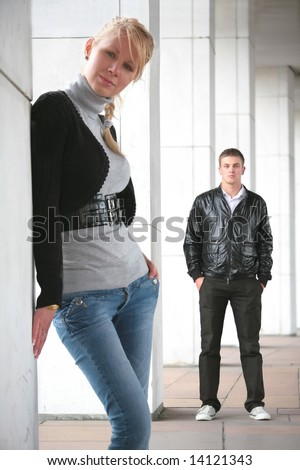 girl and young man peer into lens of the camera