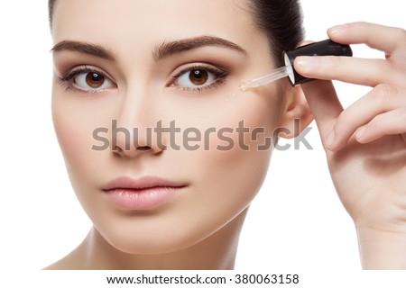 Girl applying eye serum - stock photo