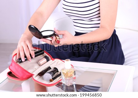 Girl applying make up on home interior background - stock photo