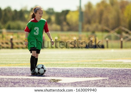 Girl at a soccer practice running with the ball - stock photo