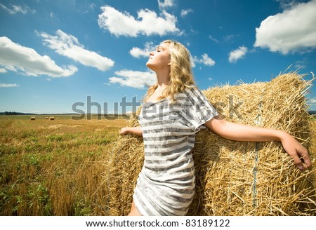 Girl at a stack of straw against a field and the sky