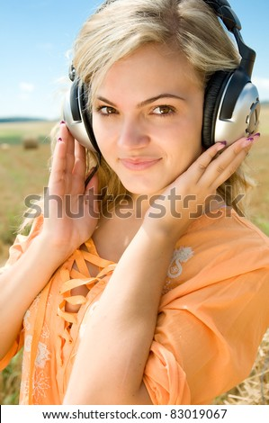 Girl at a stack of straw listening to music