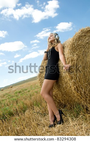 Girl at a stack of straw listening to music against a field and the sky