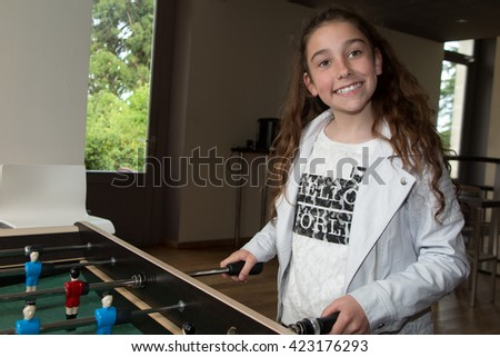 Girl at a table football looking happy