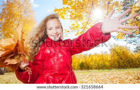 Girl at autumn. Child with leaf at park - stock photo