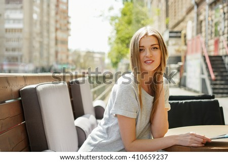 Girl at coffee shop on the street in the spring.