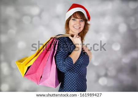 Girl at funny hat and with three paper bags at light background