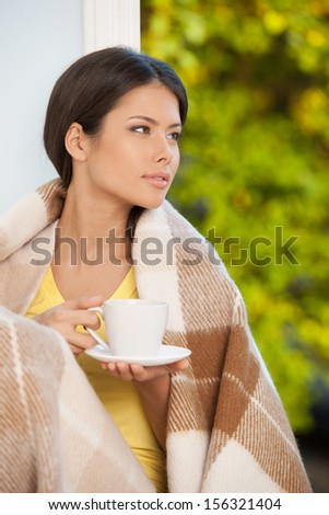 Girl at home. Beautiful young woman sitting on the windowsill and drinking coffee - stock photo