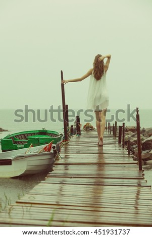 Girl at pier is looking for a place to escape during rainy day