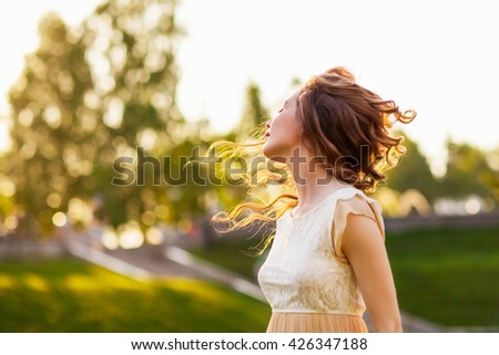 Girl at sunset with flying hair - stock photo