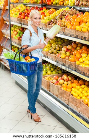Girl at the market choosing fruits and vegetables hands cabbage and full of purchases hand cart - stock photo