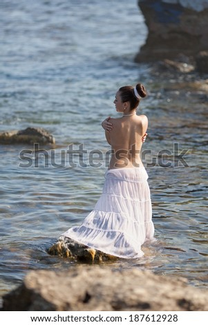 Girl at the sea. Wet young woman posing in the sea, rear view