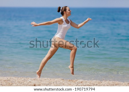 Girl at the sea. Young woman in white hiding her torso smiling - stock photo