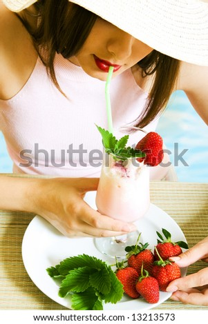 Girl at vacation with cold strawberry cocktail - stock photo