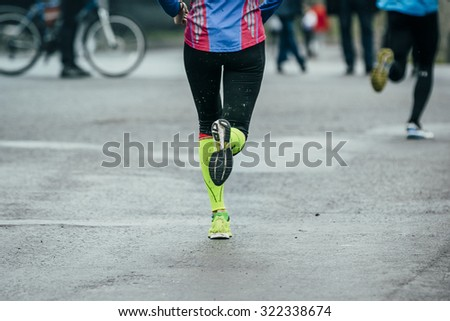 girl athlete running on the wet road, their feet on dirt. view from back - stock photo