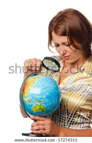 Girl attentively examines the globe through a magnifier