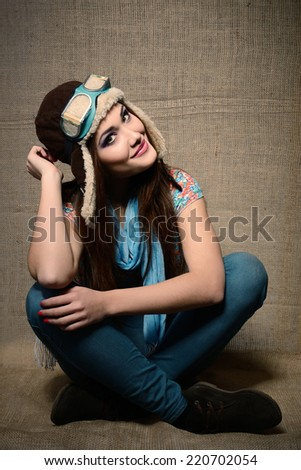 Girl - aviator, portrait of young woman in pilot uniform over canvas background - stock photo
