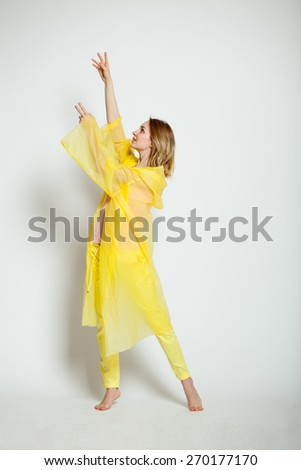 girl back in the yellow points to something - stock photo