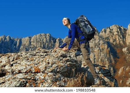 girl backpacker climbing in mountains - stock photo