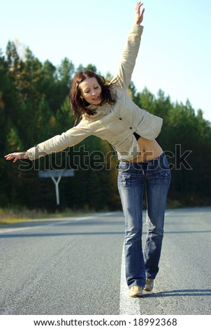 Girl balance on the road in forest - stock photo