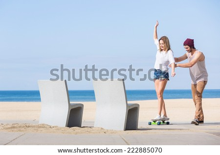 Girl balancing on a skateboard while a boy is teaching her on a boulevard with a beach and sea in the background - stock photo