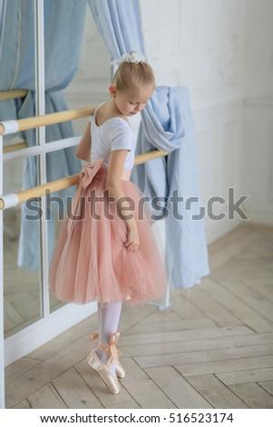 girl ballerina standing in pointes in the mirror corrects pink fluffy skirt