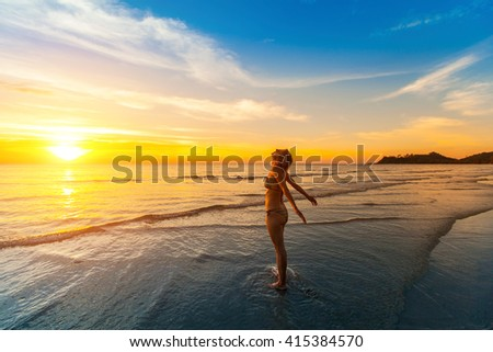 Girl basking in the sun on the beach near the water during sunset. - stock photo