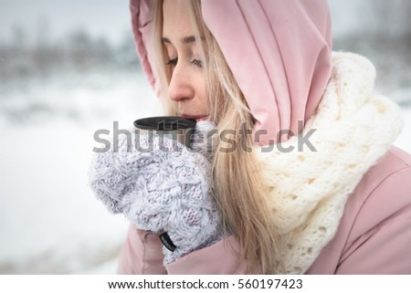 girl basking in the winter of drink from a thermos