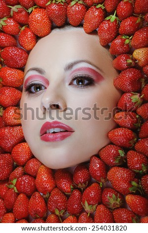 Girl beauty face with fresh red  strawberries frame - stock photo