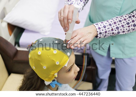 Girl before procedure electroencephalography, nurse using syringe introduces special gel for electrodes located in cap of electroencephalogram - stock photo