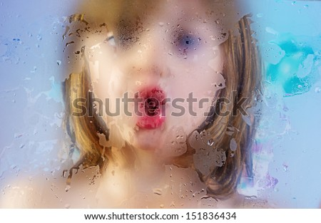 girl behind a dewy glass in a shower