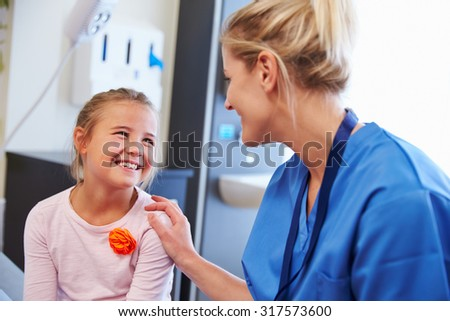 Girl Being Reassured By Nurse In Hospital Room - stock photo