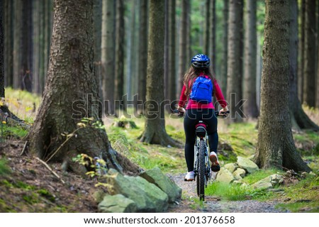 Girl biking on forest trails - stock photo