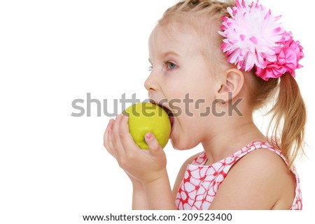 girl biting an apple mouth wide open.The concept of childhood and child development - stock photo