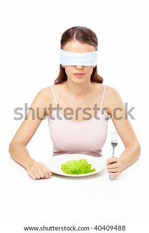 Girl blindfold sits before plate with salad leaf, isolated - stock photo