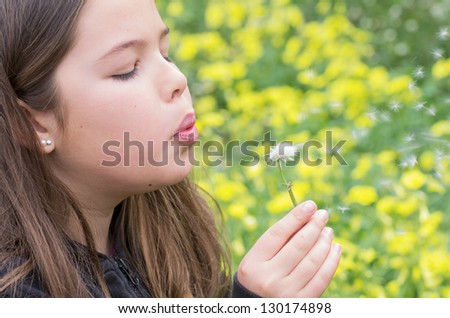 girl blowing a flower on a wonderful floral background