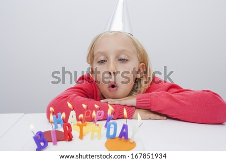 Girl blowing birthday candles at table in house - stock photo