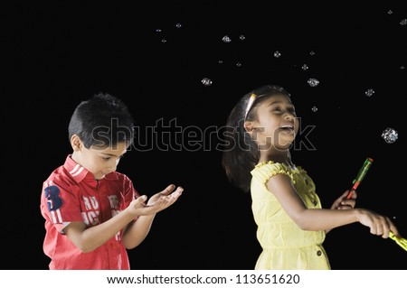 Girl blowing bubbles and a boy looking at his palm - stock photo