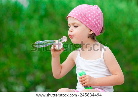 Girl blowing bubbles. cute little girl blowing soap bubbles - green background - stock photo