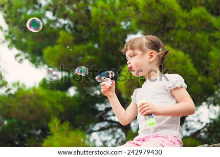 Girl blowing bubbles. lovely little girl blowing soap bubbles. - stock photo