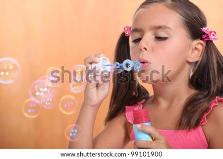 Girl blowing bubbles of soap - stock photo