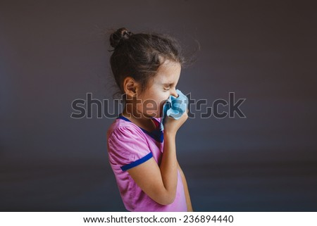 girl blowing her nose sneezes into a handkerchief on a gray background - stock photo