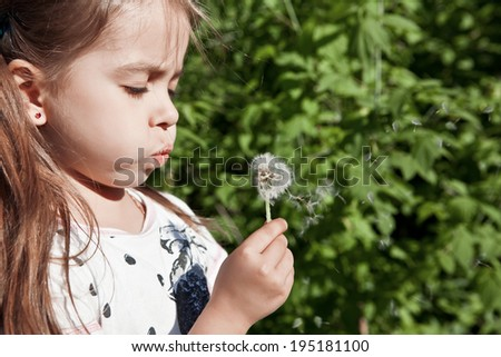Girl blowing on dandelion - stock photo