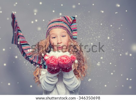 Girl blowing on the snows. Happy child in winter clothes. Studio shot - stock photo